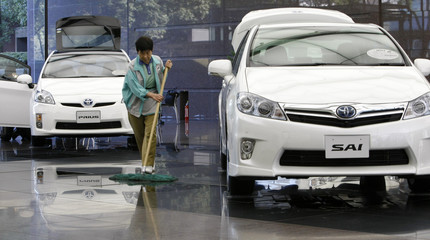 A worker cleans lobby where Toyota's cars are displayed in their office in Tokyo