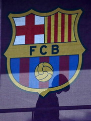 A silhouette of a woman walks past behind a FC Barcelona's logo at Camp Nou stadium in Barcelona