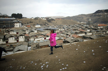 A girl runs down a hill near a temple during Tibetan New Year celebrations in Langmusixiang