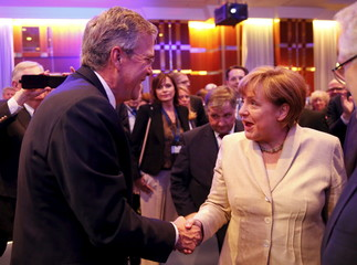 German Chancellor Angela Merkel shakes hand with former Florida Governor and potential Republican presidential candidate Bush after he addressed the CDU party economic council in Berlin