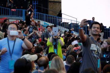 Attendees take photographs during the Google I/O 2016 developers conference in Mountain View, California