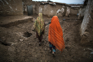 Girls walk on a muddy lane towards their house in a slum on the outskirts of Islamabad