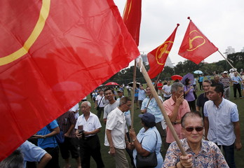 Supporters of the Workers' Party carry flags as they wait for their candidates at a nomination center ahead of the general elections in Singapore