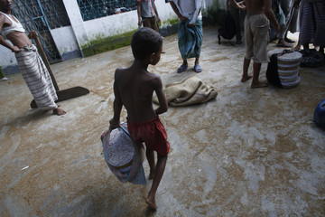 Boy carries stack of cigarettes as he works in a small 'bidi' factory at Haragach in Rangpur district