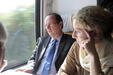 Francois Hollande, Socialist Party candidate for the 2012 French presidential election, speaks with campaign staff on train to Laon