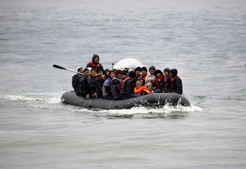 Afghan migrants arrive by a raft during rain storm on the Greek island of Lesbos