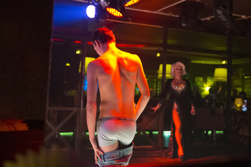 A man strips during a drag performance at Mayak, a gay cabaret club in Sochi