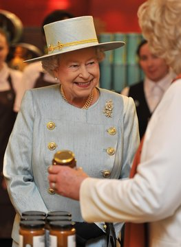 Britain's Queen Elizabeth is shown jars of preserves at the Fortnum and Mason store in central London