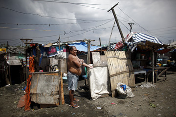 A resident takes a shower outside his house in a community of makeshift homes built under and around a busy bridge in Paranaque