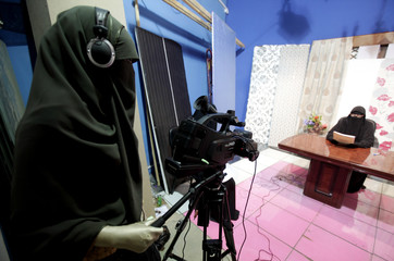 A video woman records a program in a studio of a new TV channel which is being managed and run exclusively by women who wear the full veil, to be launched this weekend, in Cairo