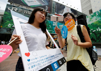 Members of SEALDs hold an Instagram frame and placards calling on youths to vote in the July 10 upper house election, in Shibuya district in Tokyo
