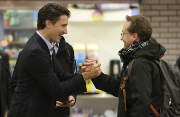 Liberal leader and prime minister-designate Justin Trudeau greets people at a subway station in his riding in Montreal