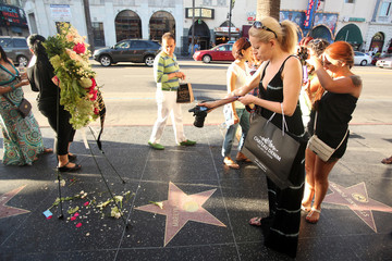 Fans take pictures of a memorial on Marilyn Monroe's Hollywood Walk of Fame Star on the 50th Anniversary of her death in Hollywood