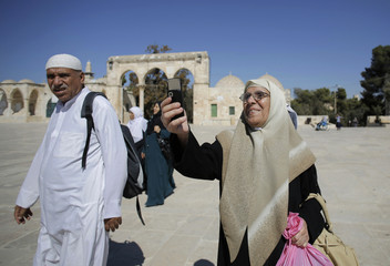 A Palestinian woman from Gaza takes a picture during a visit at the compound known to Muslims as Noble Sanctuary and to Jews as Temple Mount in Jerusalem's Old City