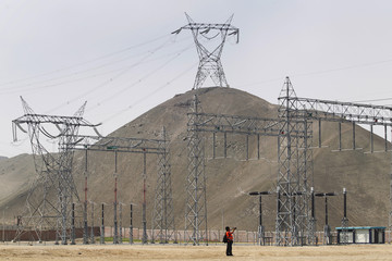 A man takes pictures of pylons at the Termochilca thermoelectric power plant during its inauguration ceremony at Chilca district