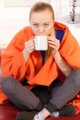 Woman lying on sofa under blanket drinking tea