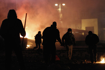 Pro-European protesters run past burning vehicles during clashes with Ukranian riot police in Kiev