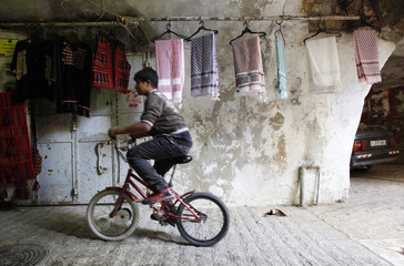 A Palestinian youth cycles past keffiya headdresses for sale that were made at the Hirbawi textile factory in the West Bank city of Hebron