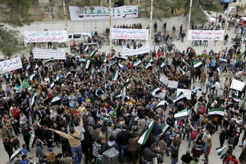 Protestors carry Free Syrian Army flags and chant slogans during an anti-government protest in the town of Marat Numan in Idlib province