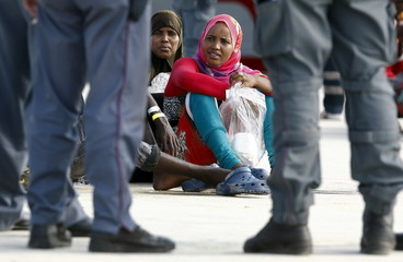 Migrants wait after disembarking from the Italian Navy vessel Cigala Fulgosi in the Sicilian harbour of Augusta