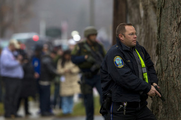 A Newtown police officer stands behind a tree with his gun drawn as a Connecticut State Police SWAT team inspects the St. Rose of Lima Catholic church in Newtown, Connecticut