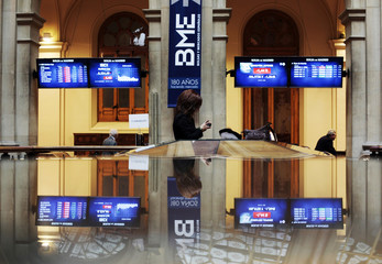 A TV reporter checks her phone as traders look at computer screens in the background at Madrid's bourse
