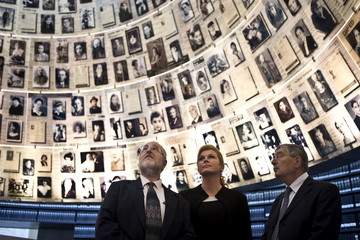 Croatian President Grabar-Kitarovic stands next to Director of Yad Vashem Shalev and Director of Yad Vashem libraries Rozett look at pictures during a visit to Yad Vashem's Holocaust History Museum in Jerusalem