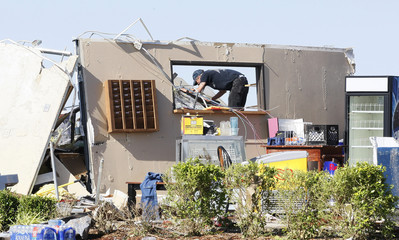 A man is framed by the kitchen pass-through window on the only kitchen wall still remaining as he checks tornado damage in El Reno