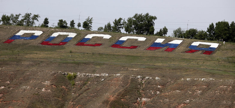 """The word """"Russia"""" created with marble stones painted in colours of national  flag is seen on a slope of the Karaulnaya Sopka hill in the Siberian city of Krasnoyarsk"""