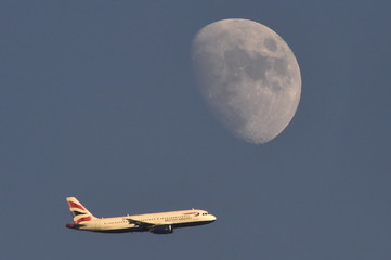 A British Airways passenger plane flies in the sky with the moon seen in the background, in London, Britain