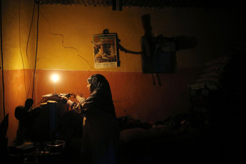 Palestinian woman lights a candle inside her house during a power cut in Jabalya in the northern Gaza Strip