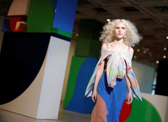 A model walks past geometric designs during a runway show by Ginger and Smart at the Art Gallery of New South Wales during Fashion Week Australia in Sydney