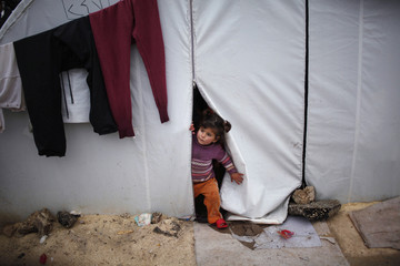 A Syrian refugee child looks out of her family tent at Bib Salam refugee camp in Syria near the Turkish border
