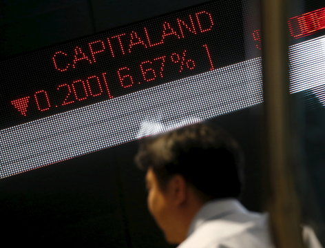 Man passes a stock index board showing property developer Capitaland losing 6.67 percent at the Singapore Exchange in the central business district