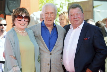 Actors Shirley MacLaine, Christopher Plummer and William Shatner pose for photographers following a handprint and footprint ceremony honoring Plummer at the TCL Chinese Theatre in Los Angeles