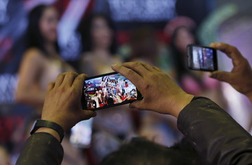 """Visitors take pictures of exotic dancers using their cell phones at the """"Sex and Entertainment Expo"""" adult exhibition at the Palacio de los Deportes in Mexico City"""