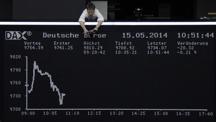 A photographer photographs the curve of the German share price index DAX board at the Frankfurt stock exchange