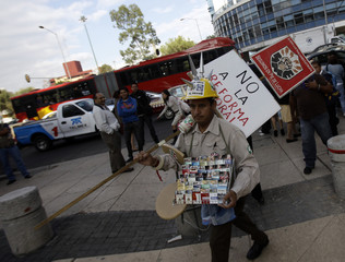 A street vendor, selling cigarettes, carries a poster outside the Mexican senate building