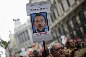 A man holds a placard with a picture of Spain's PM Rajoy during Labour Day demonstration in central Madrid