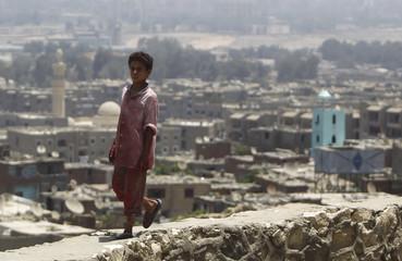 Karim, 15, walks on a wall on a mountain near Manshiyet Nasser shanty town in eastern Cairo