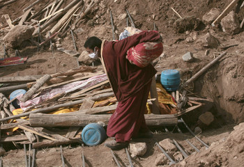 A Tibetan monk carries a corpse for a mass cremation of earthquake victims in the town of Gyegu in Yushu County