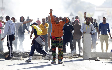 Demonstrators stand behind barricades during a protest against what demonstrators said was government's failure to provide adequate housing facilities and other basic services, in Cape Town's Langa township