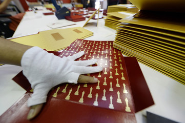 Workers assemble envelopes and announcement award cards bearing the names of Oscar winners for the 87th Academy Awards in Los Angeles
