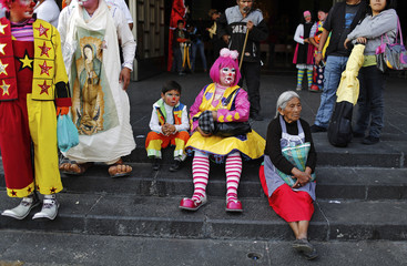 An elderly woman rests next to clowns after a mass at the Basilica of Our Lady of Guadalupe in Mexico City