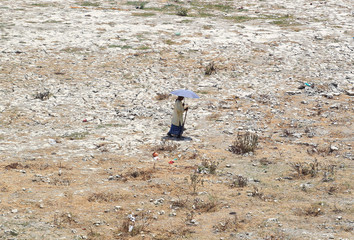 A man holds an umbrella as he walks on the banks of the river Ganga on a hot summer day in Allahabad