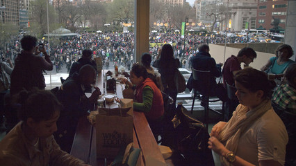 Patrons eat in a restaurant overlooking New York's Union Square where a protest was being held to demand justice for the killing of Florida teen Martin