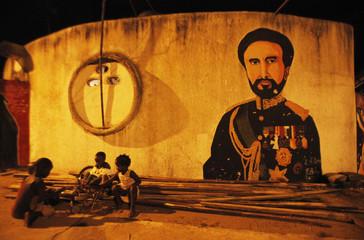 Children play near a portrait of Haile Selassie in Vridi's Village Rasta, Abidjan