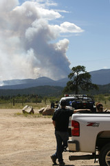 People wait beside their truck as the High Park Fire burned in the background in Fort Collins