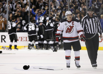 New Jersey Devils left wing Parise leaves the ice as the Los Angeles Kings celebrate in the background after the Kings defeated the Devils in Game 6