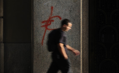 A man walks past a euro symbol painted in red on a branch of Santander bank in central Madrid